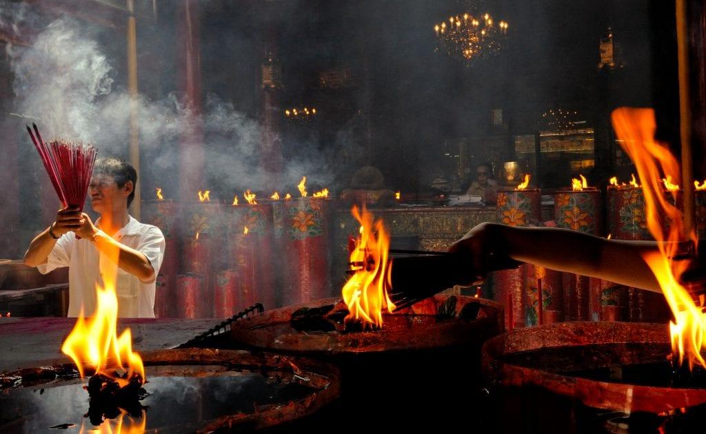 Man burning incense in a temple in Glodok, Jakarta