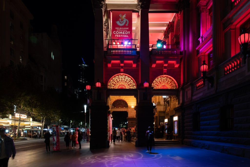 The Melbourne International Comedy Festival poster at night
