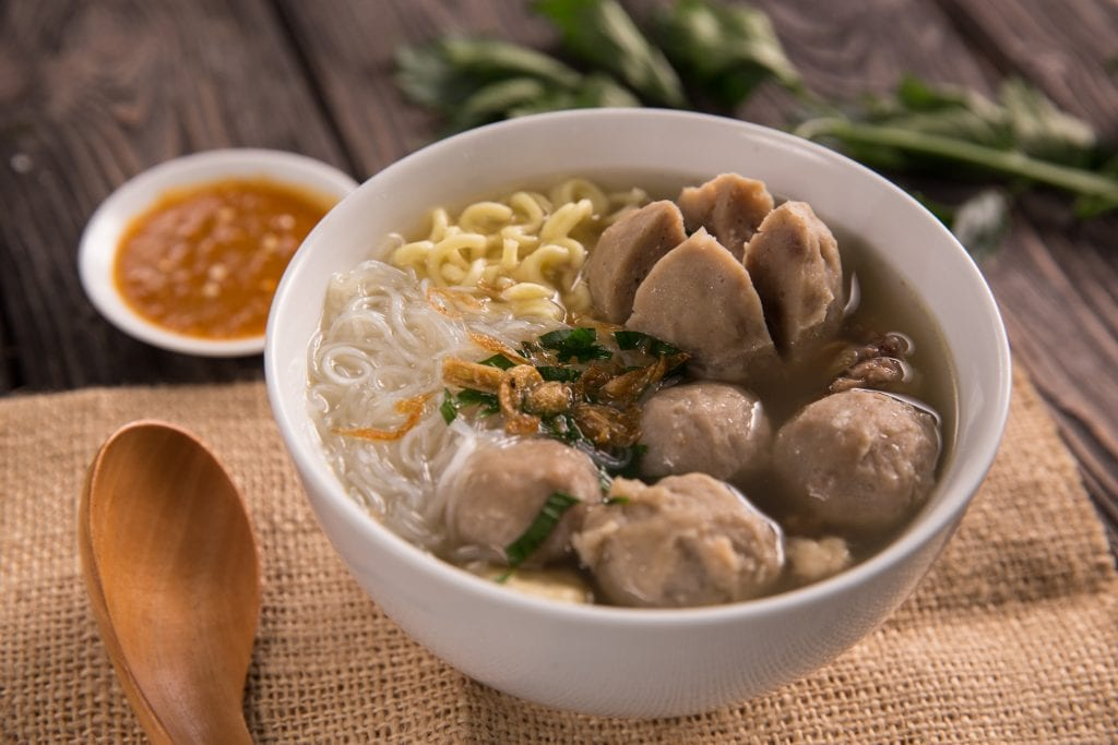 Bakso meatballs with noodles and soup and sambal in the background