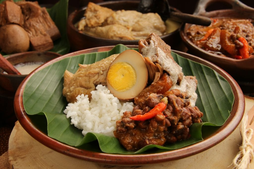 Nasi Gudeg on palm leaves with dish components in background